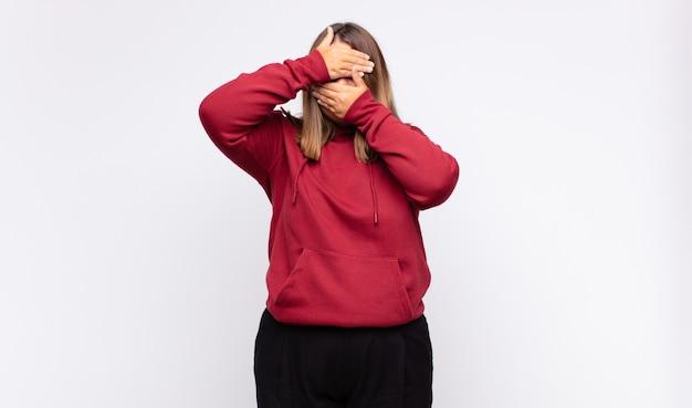 Jonge blonde vrouw die gezicht bedekt met beide handen en nee zegt tegen de camera! afbeeldingen weigeren of foto's verbieden