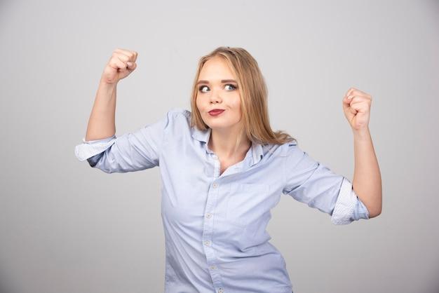 Jonge blonde vrouw die haar spieren laat zien aan de camera