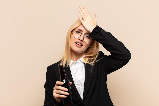 Jonge blonde vrouw die handpalm naar voorhoofd steekt en denkt oeps, na een domme fout te hebben gemaakt of zich dom te voelen