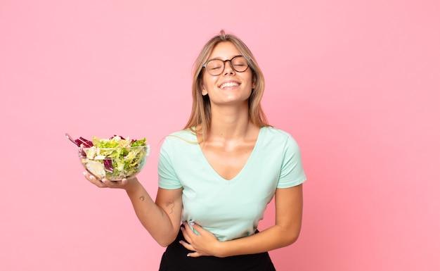 Jonge blonde vrouw die hardop lacht om een hilarische grap en een salade vasthoudt