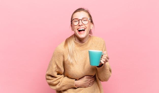 Jonge blonde vrouw die hardop lacht om een hilarische grap, zich gelukkig en opgewekt voelt, plezier heeft. koffie concept
