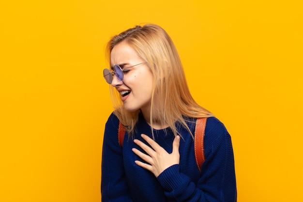 Jonge blonde vrouw die hardop lacht om een of andere hilarische grap, zich gelukkig en opgewekt voelt, plezier heeft