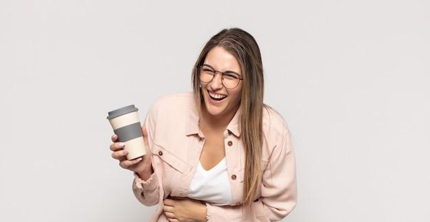 Jonge blonde vrouw die hardop lacht om een of andere hilarische grap, zich gelukkig en opgewekt voelt