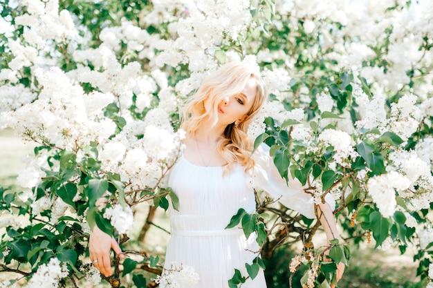 Jonge blonde vrouw die in witte kleding in bloeiend park genieten van