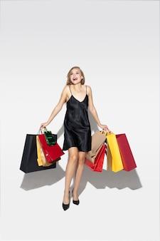Jonge blonde vrouw die in zwarte kleding op wit winkelt