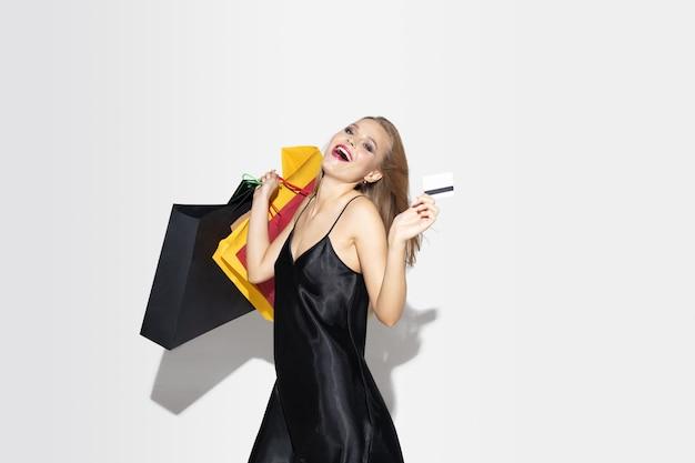 Jonge blonde vrouw die in zwarte kleding op witte muur winkelt