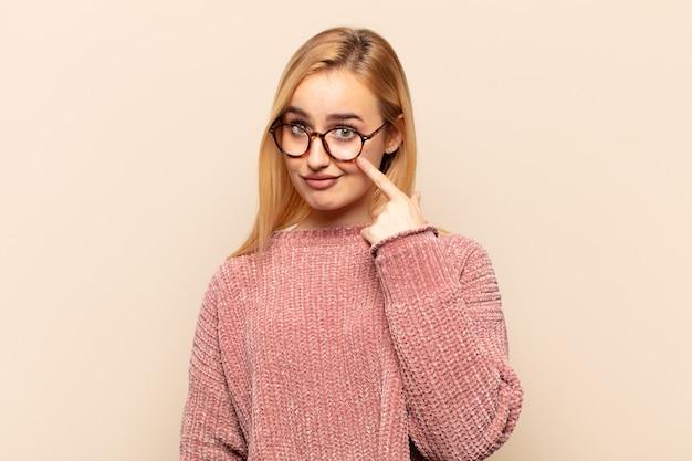 Jonge blonde vrouw die je in de gaten houdt, niet vertrouwt, kijkt en alert en waakzaam blijft