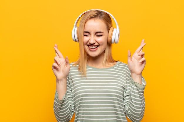 Jonge blonde vrouw die lacht en angstig beide vingers kruist, zich zorgen maakt en geluk wenst of hoopt