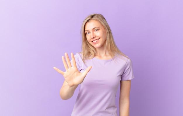 Jonge blonde vrouw die lacht en er vriendelijk uitziet, met nummer vijf