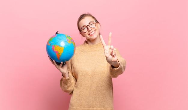 Jonge blonde vrouw die lacht en er vriendelijk uitziet, nummer twee of seconde toont met de hand naar voren, aftellend. wereld concept