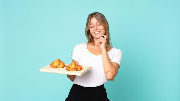 Jonge blonde vrouw die lacht met een gelukkige, zelfverzekerde uitdrukking met de hand op de kin en een croissantblad vasthoudt