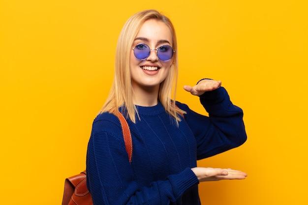 Jonge blonde vrouw die lacht, zich gelukkig, positief en tevreden voelt, voorwerp of concept op exemplaarruimte vasthoudt of toont