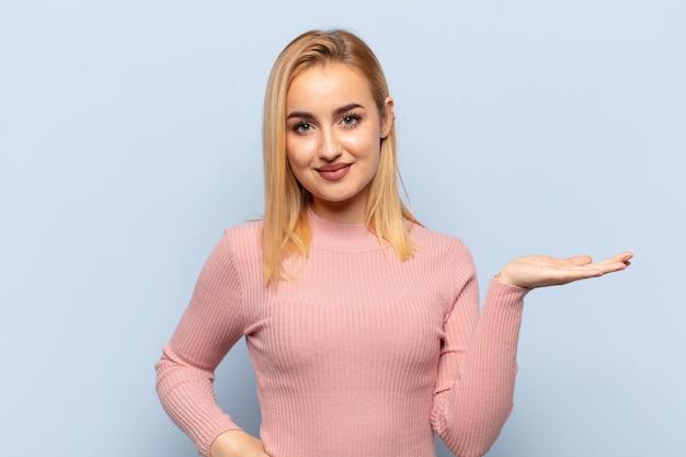 Jonge blonde vrouw die lacht, zich zelfverzekerd, succesvol en gelukkig voelt, concept of idee toont op kopie ruimte aan de zijkant