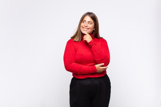 Jonge blonde vrouw die met een gelukkige, zelfverzekerde uitdrukking glimlacht met hand op kin, zich afvraagt en naar de kant kijkt