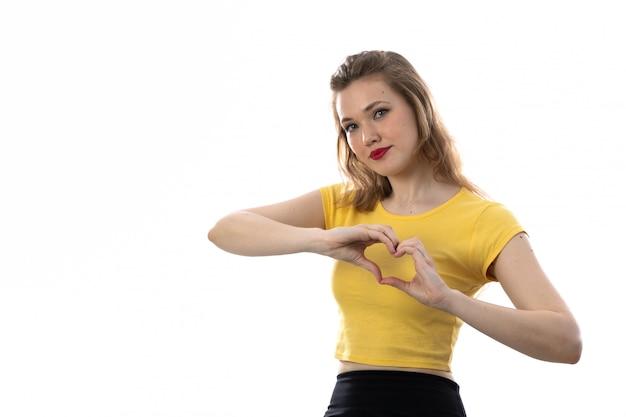 Jonge blonde vrouw die met gele t-shirt een hart met haar handen maakt