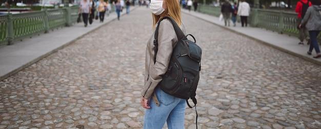 Jonge blonde vrouw die met rugzak in de stad loopt en een gezichtsmasker draagt