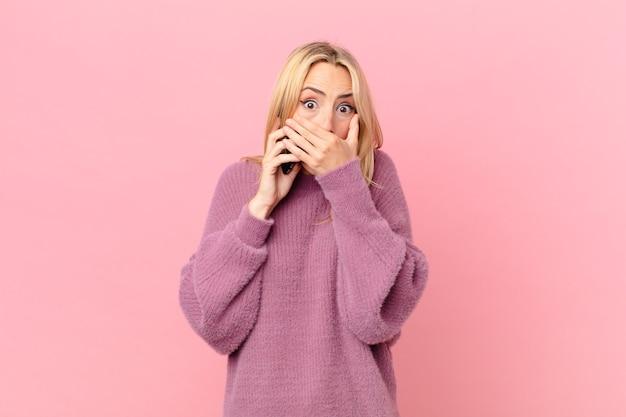 Jonge blonde vrouw die mond bedekt met handen met een geschokt en pratend met een smartphone