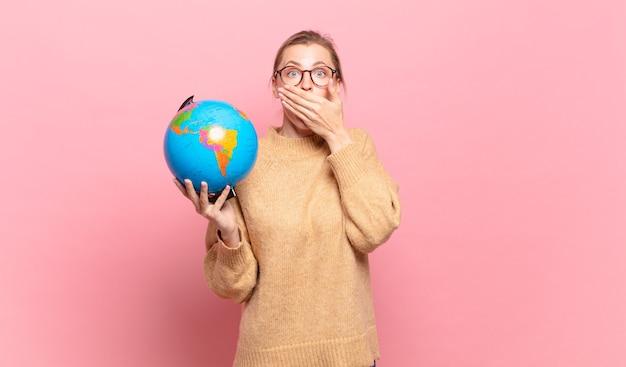 Jonge blonde vrouw die mond bedekt met handen met een geschokte, verbaasde uitdrukking, een geheim houdt of oeps zegt. wereld concept