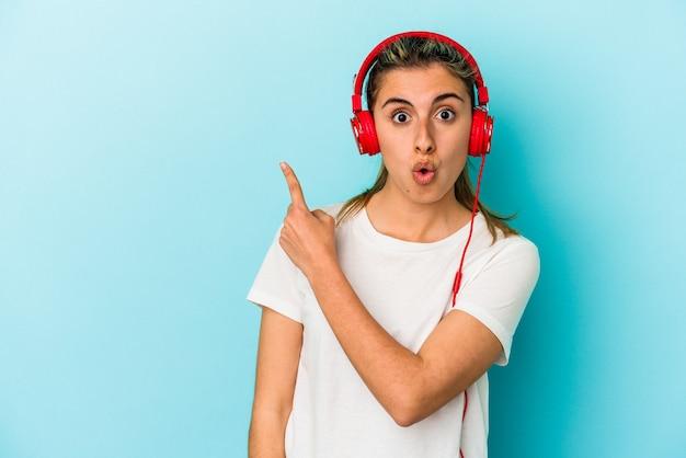 Jonge blonde vrouw die naar muziek luistert op een koptelefoon geïsoleerd op een blauwe achtergrond die naar de zijkant wijst