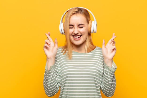 Jonge blonde vrouw die nerveus en hoopvol is, vingers kruist, bidt en hoopt op geluk