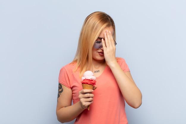 Jonge blonde vrouw die ogen bedekt met handen met een droevige, gefrustreerde blik van wanhoop, huilend, zijaanzicht