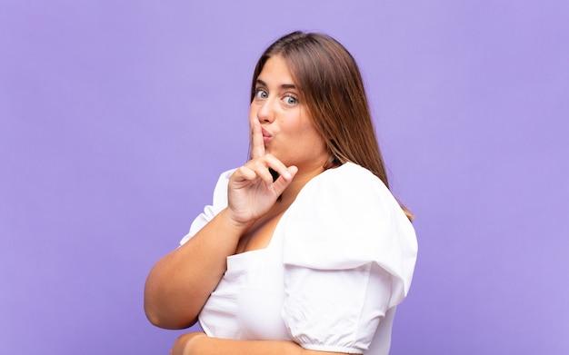 Jonge blonde vrouw die om stilte en stilte vraagt, met vinger voor mond gebaart, shh zegt of een geheim houdt