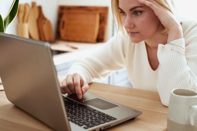 Jonge blonde vrouw die op de laptop thuis werkt, thuis winkelen