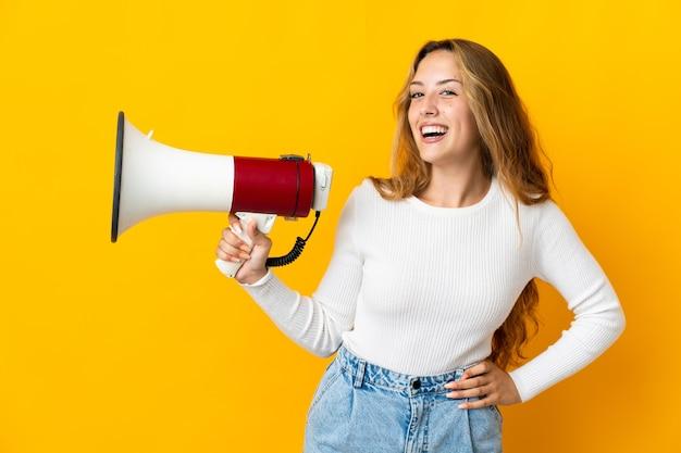 Jonge blonde vrouw die op gele muur wordt geïsoleerd die een megafoon houdt en glimlacht