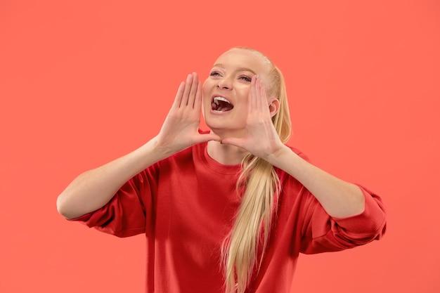 Jonge blonde vrouw die op koraalachtergrond gilt