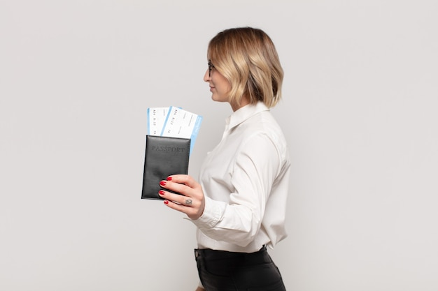 Jonge blonde vrouw die op profielweergave ruimte vooruit wil kopiëren, denken, zich voorstellen of dagdromen
