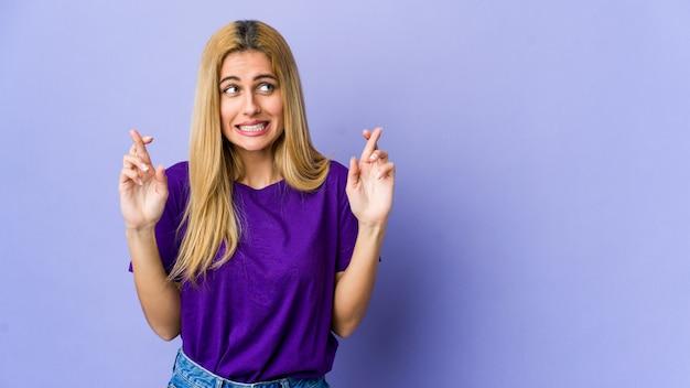 Jonge blonde vrouw die op purpere kruisende vingers wordt geïsoleerd voor het hebben van geluk