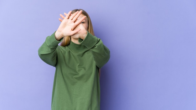 Jonge blonde vrouw die op purpere muur wordt geïsoleerd die twee gekruiste wapens houdt, ontkenningsconcept.