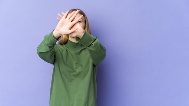 Jonge blonde vrouw die op purpere muur wordt geïsoleerd die twee gekruiste wapens houdt, ontkenningsconcept