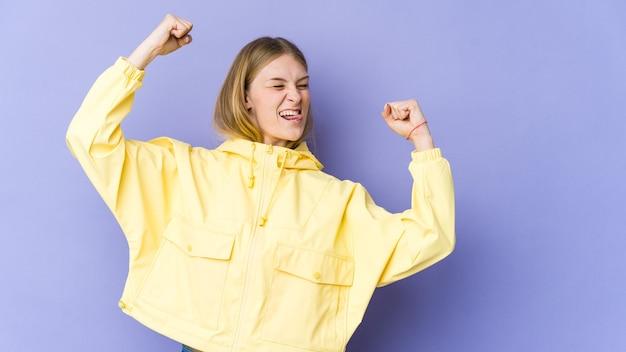 Jonge blonde vrouw die op purpere muur wordt geïsoleerd die vuist opheft na een overwinning, winnaarconcept.