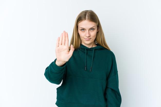 Jonge blonde vrouw die op wit wordt geïsoleerd dat zich met uitgestrekte hand bevindt die stopbord toont, dat u verhindert.