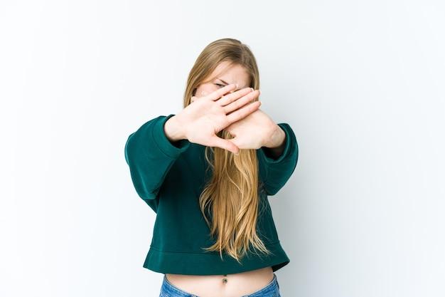Jonge blonde vrouw die op witte muur wordt geïsoleerd die zich met uitgestrekte hand bevindt die stopbord toont, dat u verhindert