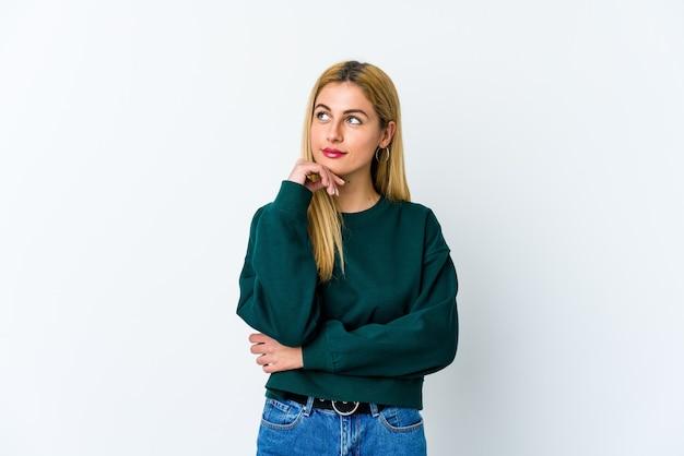 Jonge blonde vrouw die opzij kijkt met een twijfelachtige en sceptische uitdrukking.