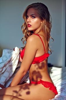 Jonge blonde vrouw die rode lingerie op bed in de ochtend draagt