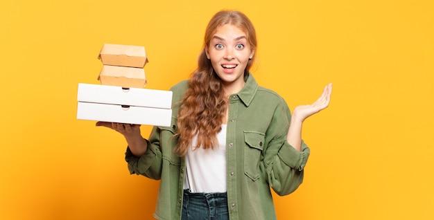 Jonge blonde vrouw die snel voedsel wegneemt