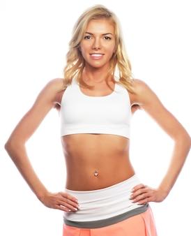 Jonge blonde vrouw die sportkleding draagt, geïsoleerd tegen een witte achtergrond