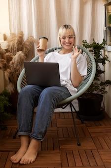 Jonge blonde vrouw die vanuit huis in haar stoel werkt