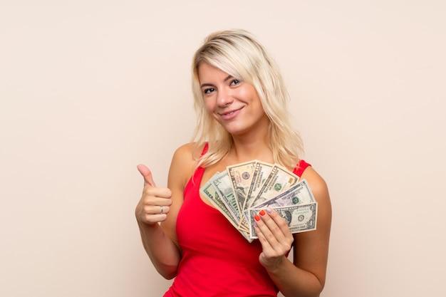 Jonge blonde vrouw die veel geld neemt