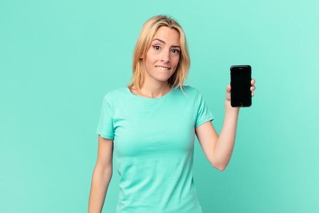 Jonge blonde vrouw die verbaasd en verward kijkt en een smartphone vasthoudt