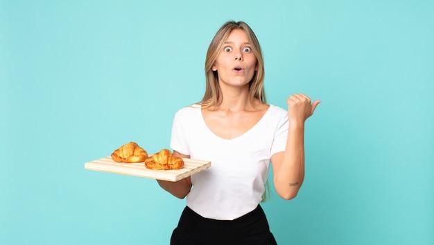 Jonge blonde vrouw die verbaasd kijkt in ongeloof en een croissantblad vasthoudt