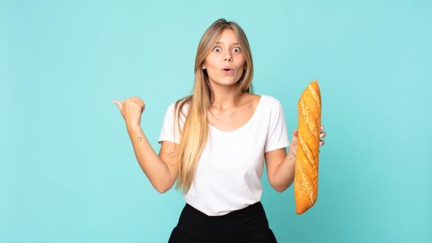 Jonge blonde vrouw die verbaasd kijkt in ongeloof en een stokbrood vasthoudt