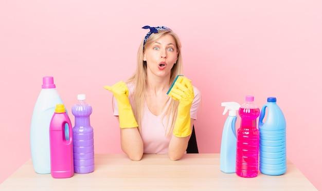 Jonge blonde vrouw die verbaasd kijkt in ongeloof. huishoudster concept