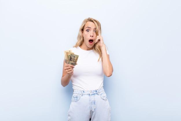 Jonge blonde vrouw die verrast, met open mond, geschokt kijkt, die een nieuwe gedachte, een idee of een concept met dollarbankbiljetten realiseert