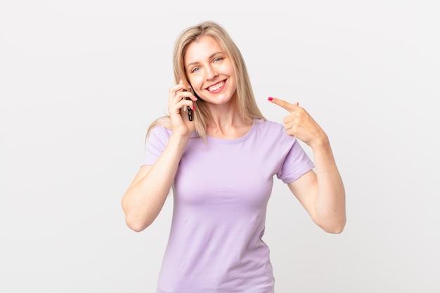 Jonge blonde vrouw die vol vertrouwen glimlacht, wijst naar een brede glimlach en belt met een smartphone