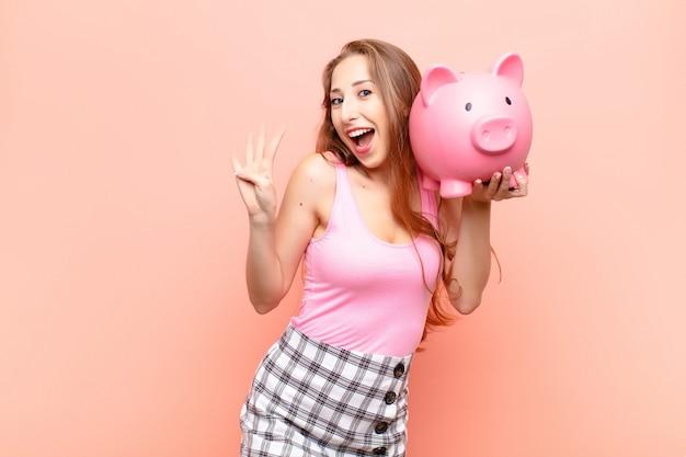 Jonge blonde vrouw die vriendelijk glimlacht en kijkt, nummer vier of vierde met vooruit hand toont, aftellend met een spaarvarken