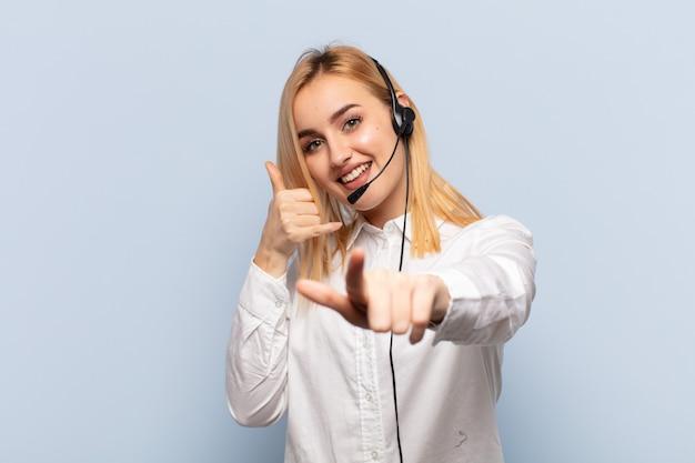 Jonge blonde vrouw die vrolijk glimlacht en wijst terwijl het u later gebaren maakt, pratend aan de telefoon